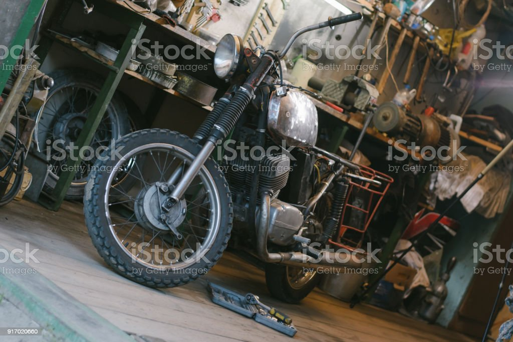 Old vintage motorcycle, which needs to be repaired, in the workshop, with set of tools stock photo