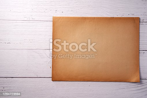 891131294 istock photo Old vintage paper sheet texture on wood background 1254723594