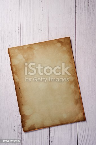 891131294 istock photo Old vintage paper sheet texture on wood background 1254723595