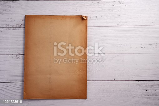 891131294 istock photo Old vintage paper sheet texture on wood background 1254723616