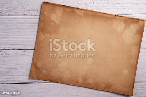 891131294 istock photo Old vintage paper sheet texture on wood background 1254723623