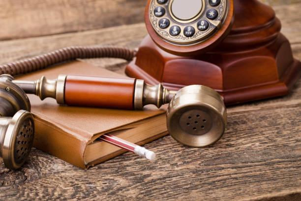 Velho monofone do telefone vintage, livro sobre fundo grunge de mesa de madeira - foto de acervo