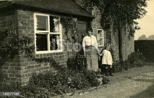 Old vintage photo of mum and daughter standing at cottage door.Black and white.