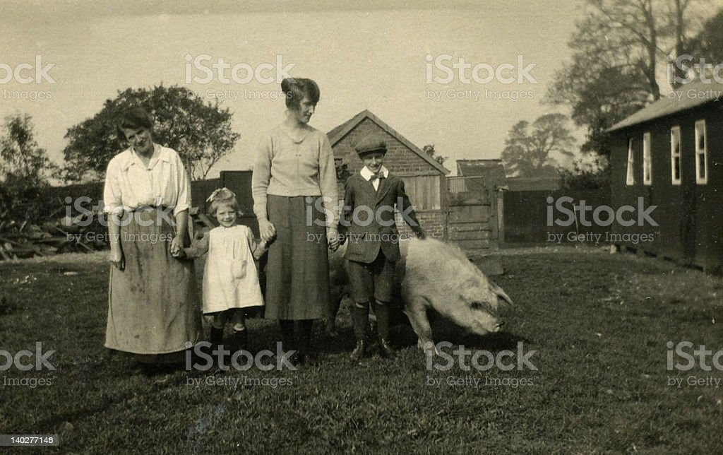 Old Vintage photo, Two Ladies and Children standing beside Pig stock photo
