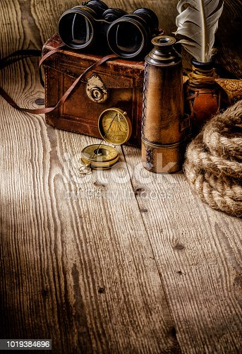 istock Old vintage retro compass, binoculars and spyglass on wooden table. 1019384696