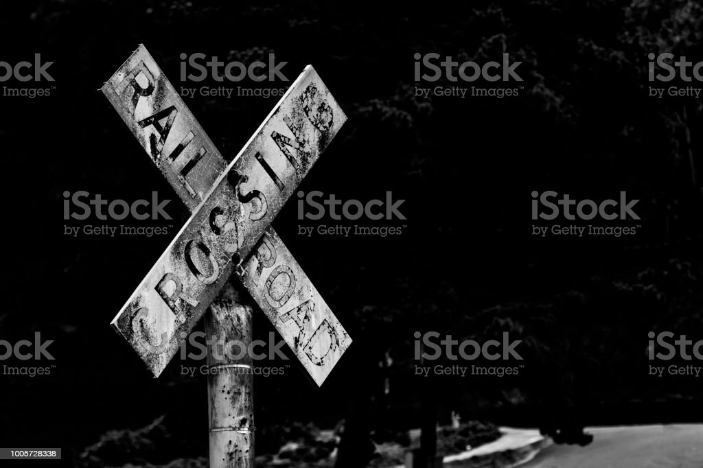 Old vintage retro distressed railroad crossing sign with worn faded text stock photo