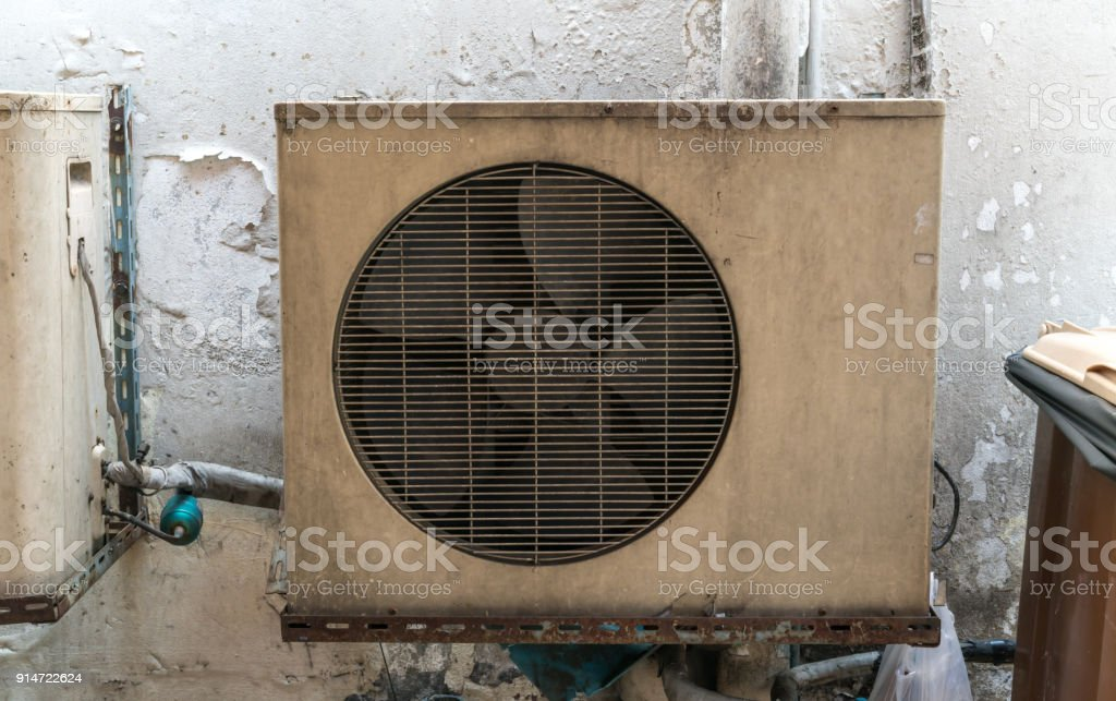 Old vintage rusting metal exterior fitted air-conditioning unit mounted on wall needing maintenance stock photo