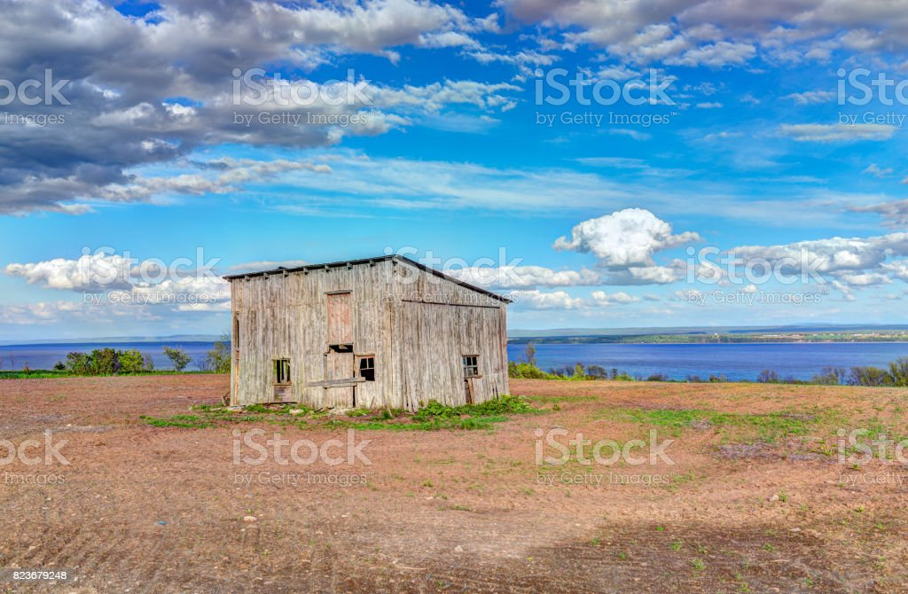 Old vintage slanted shed in summer landscape brown soil field in countryside stock photo