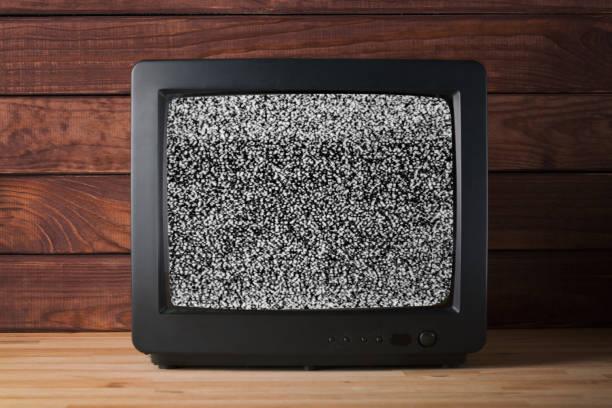 alte vintage tv set streichmusik auf holztisch againt dunklen holzwänden hintergrund mit keine signalwirkung fernsehen körnige rauschen auf dem bildschirm - error stock-fotos und bilder