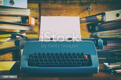 istock Old vintage typewriter and high stacks of folders on the desk 1068766624
