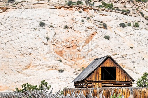 Old vintage wooden farm cabin on road in Grand Staircase Escalante National Monument with canyon formations in Utah summer