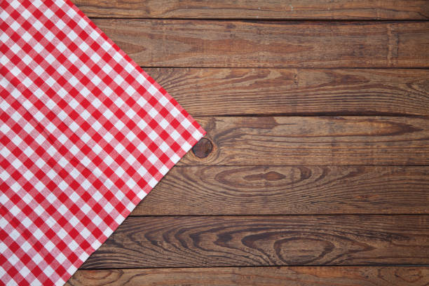Old vintage wooden table with a red checkered tablecloth. Top view mockup. Old vintage wooden table with a red checkered tablecloth. Top view mock up. red cloth stock pictures, royalty-free photos & images