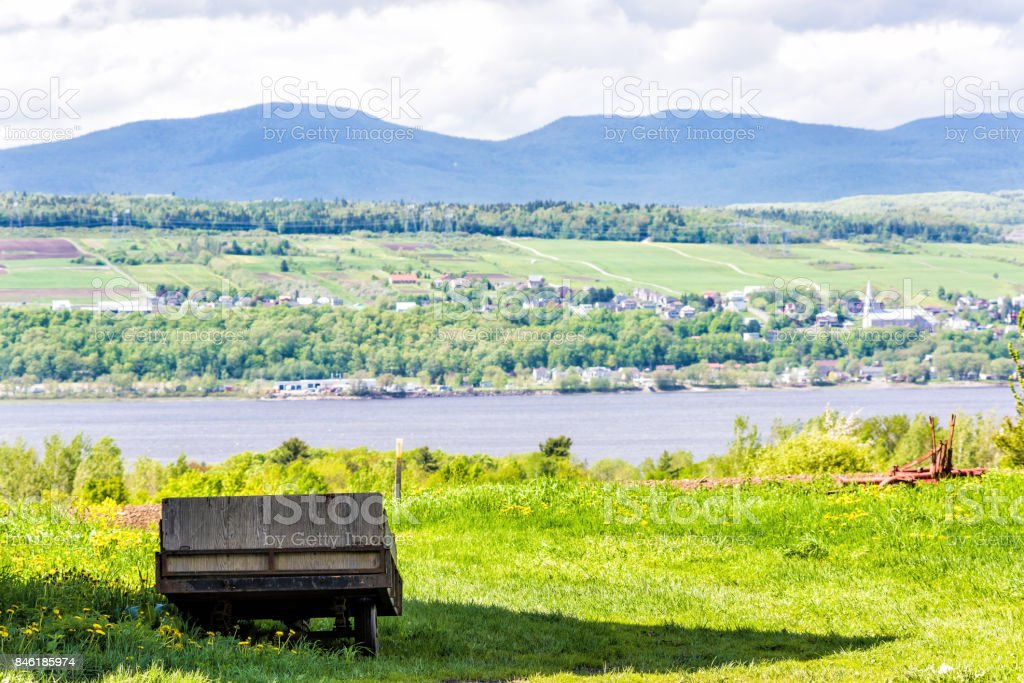 Old vintage wooden wagon overlooking Saint Lawrence river in summer landscape field in countryside with small village houses stock photo