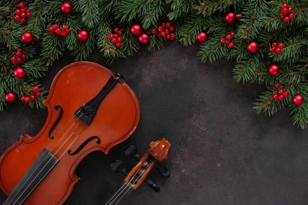Antigo violino e abeto ramos com uma decoração de Natal.  Conceito de Natal e de ano novo. Vista de cima, close-up no fundo escuro de concreto - foto de acervo