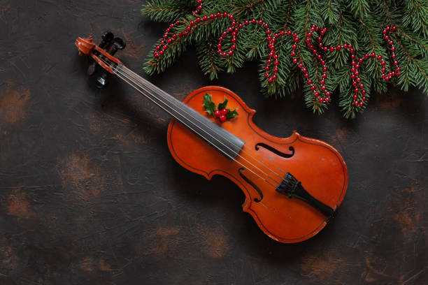 Old violin and fir-tree branches with Christmas decor. Christmas, New Year's concept. Top view, close-up on dark concrete background Old violin and fir-tree branches with Christmas decor. Christmas, New Year's concept. Top view, close-up on dark concrete background. string instrument stock pictures, royalty-free photos & images