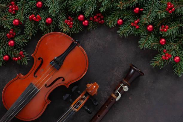 Velho violino e flauta com galhos de árvore do abeto com decoração de Natal.  Conceito de Natal e de ano novo. Vista de cima, close-up no fundo escuro de concreto - foto de acervo