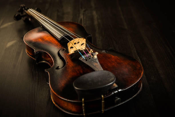 Old violin in vintage style on wood background stock photo