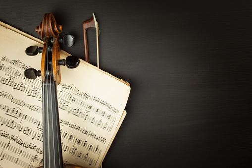 Old violin on dark wooden table