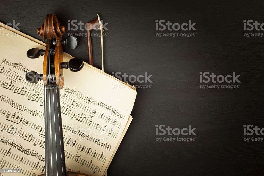 Old violin on dark wooden table stock photo