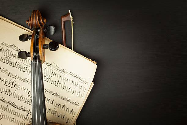 old violin on dark wooden table - classical stock photos and pictures