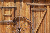 An old wagon wheel against the wall of a barn in Utah