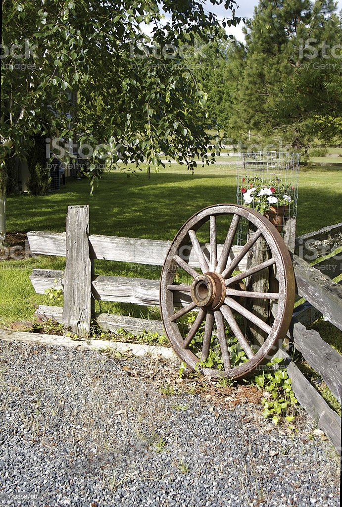 Old Wagon Wheel By The Garden Fence royalty-free stock photo