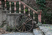 Vintage-Style Photo of a Wooden Wagon Wheel on the Side of an Exterior Concrete Staircase (Garden) - Pampanga, Philippines