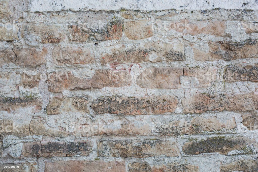 Old wall made of big stones and broken bricks. Vintage rough blocks surface background royalty-free stock photo