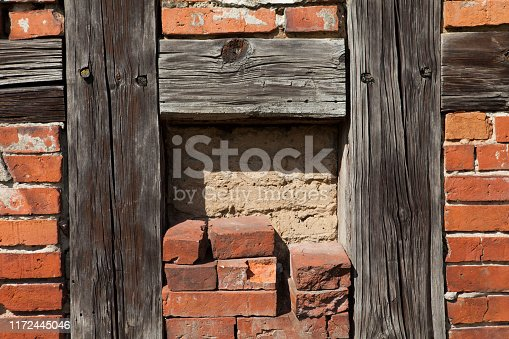 Old wall of a country house built of brick and wooden beams