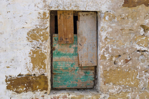 Old wall with a bricked window shuttered with old wood for background. stock photo