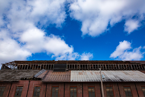 A warehouse that is in disrepair contrasted against a vivid blue sky.