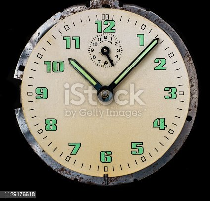 671883446 istock photo old watch dial on black background 1129176618