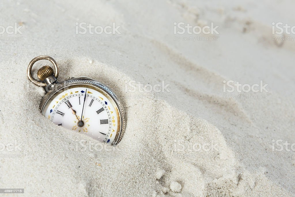 Old watch in the sand stock photo