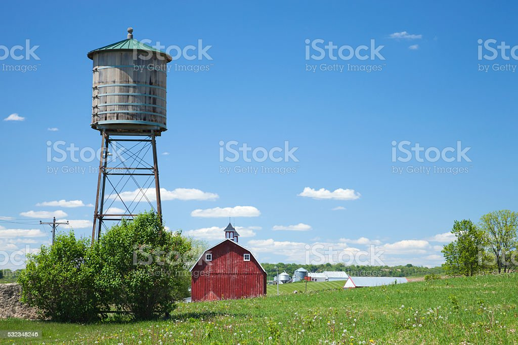 Old water cistern and red barn in rural Iowa stock photo