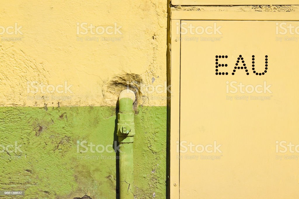 Old water metal pipes fixed with brackets in front of a plaster wall with metal box for water meter - Written in French - Royalty-free Aging Process Stock Photo