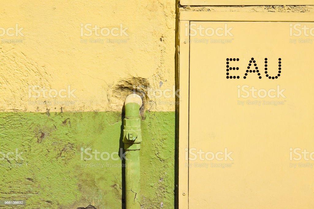 Oude metalen waterpijpen bevestigd met haakjes voor een gips muur met metalen doos voor watermeter - geschreven in het Frans - Royalty-free Aardgas Stockfoto