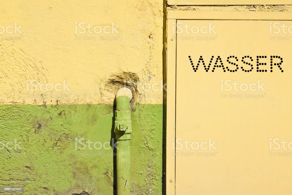 Old water metal pipes fixed with brackets in front of a plaster wall with metal box for water meter - Written in German - Royalty-free Antigo Foto de stock