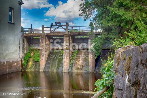 Old water run-off or sluice gate with green moss and plants growing on the surface leading to a tranquil pond below under a cloudy sunny blue sky