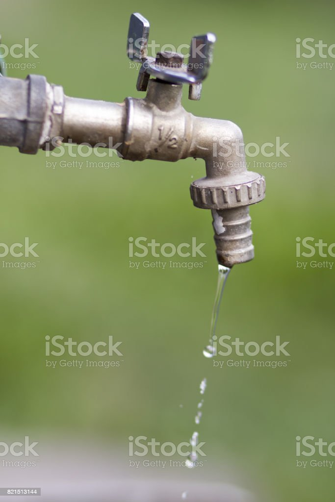Old water tap on green blur background stock photo