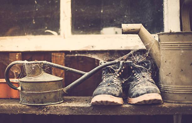 alte gießkanne und töpferwaren stiefel in schuppen - rustikaler hinterhof stock-fotos und bilder