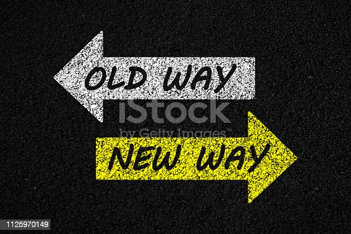 Old way or new way concept. Big yellow arrow in reverse direction in relation to big white arrow with internal text, on asphalt background.