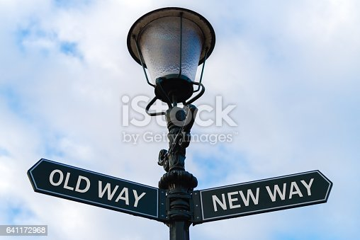 Street lighting pole with two opposite directional arrows over blue cloudy background. Old Way versus New Way concept.