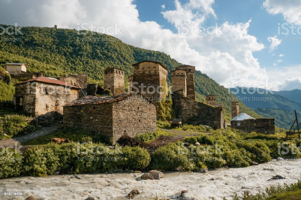 old weathered buildings against small river stream against hills, Ushguli, svaneti, georgia stock photo