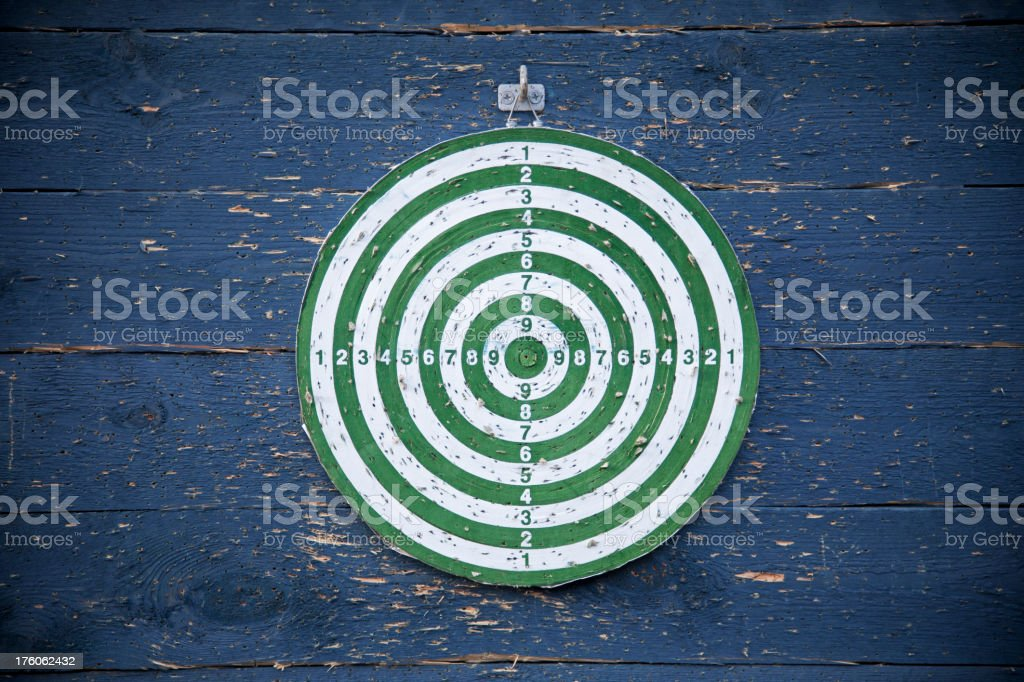 Old weathered dart target. Vignetting. Blue wall. royalty-free stock photo