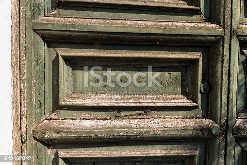 Detail of faded green door with paint peeling