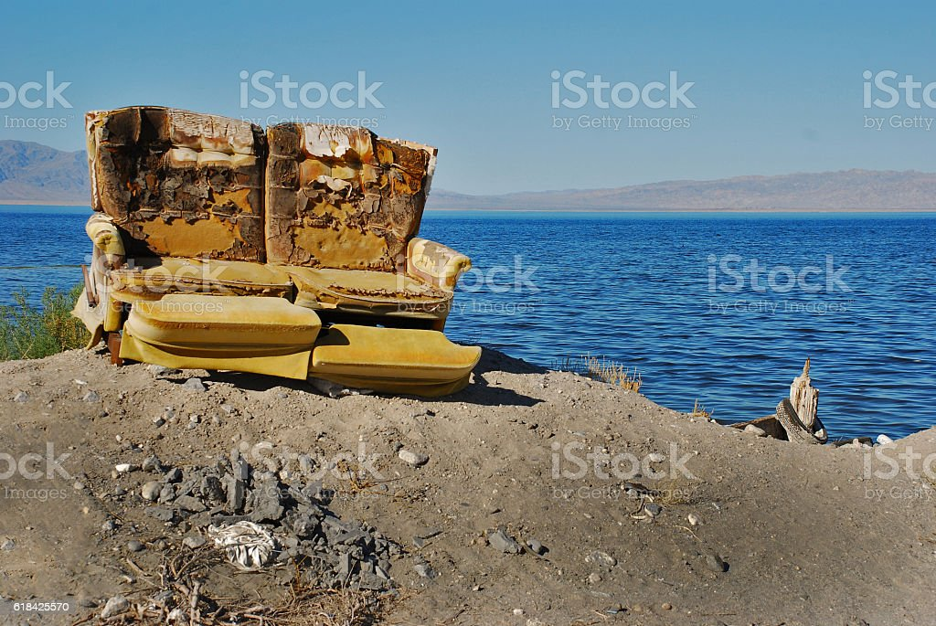 Old weathered love seat at Salton Sea stock photo