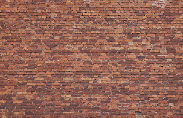 alte verwitterte rote backsteinmauer - betonwerkstein stock-fotos und bilder