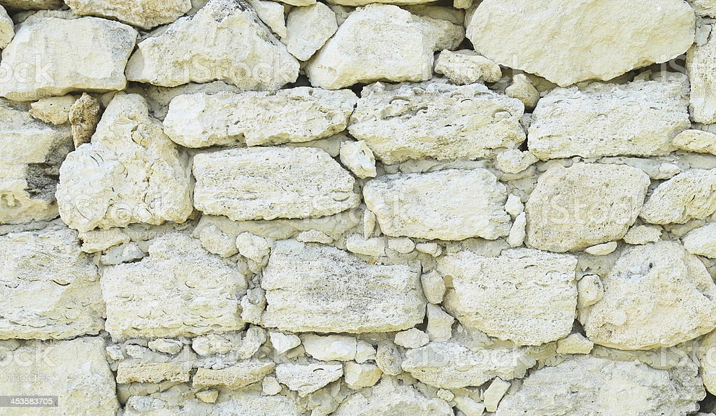Old weathered stone wall for background. Close-up. stock photo