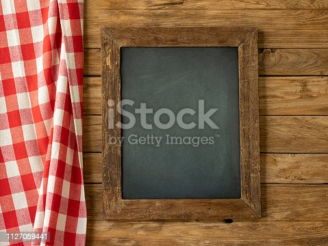 Old weathered teak wood framed blackboard hanging on an old teak wood paneled wall with a high quality cotton red gingham checked pattern tablecloth hanging next to the board. Food, menu concept etc.