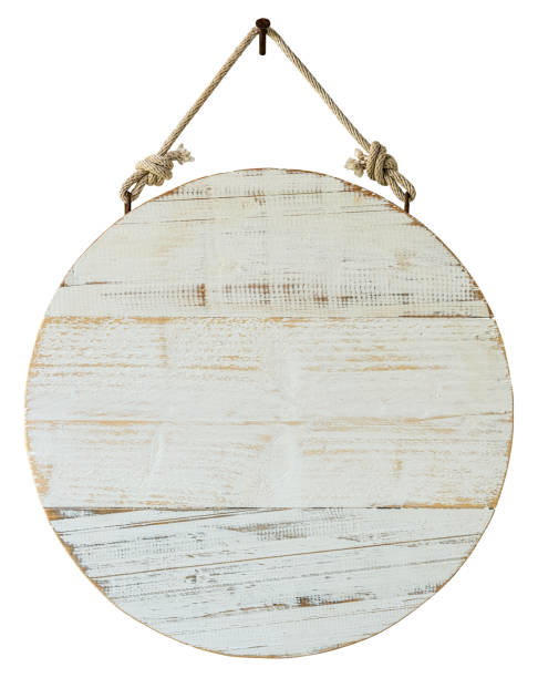 Old weathered, white, wood, circular sign/signboard panel hanging by an old rope, hanging from a rusty nail, against an isolated white background. Clipping path included. stock photo